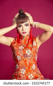 Beautiful Asian woman wearing red Chinese dress with beautiful make up and hair, Hands cover head got headache on red background, Isolated.