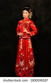 Beautiful Asian woman wearing red period wedding costume in dark background
