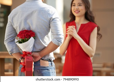 Beautiful Asian woman wearing red dress looking at her boyfriend with wide smile while he hiding bouquet of red roses and gift box behind his back
