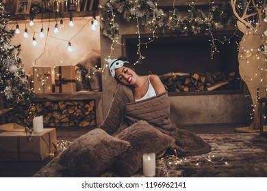 Beautiful asian woman is wearing sleeping mask and pajamas at home near christmas tree and fireplace in cozy interior. Interior with christmas decorations.