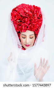 Beautiful Asian woman wearing white dress fabric decorated hair with red flowers on white background, Isolated.
