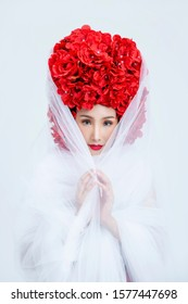 Beautiful Asian woman wearing white dress decorated red flowers on hair looking and standing on white background, Isolated.