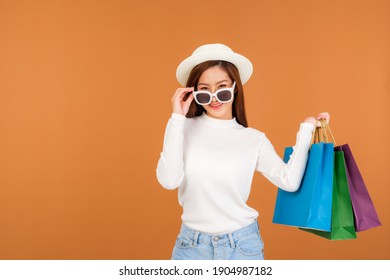 A beautiful Asian woman wearing a white long sleeve sweater and jeans, carrying a paper bag with items bought from a department store.