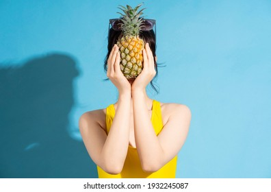 Beautiful Asian woman wearing yellow jumpsuit on blue background and eating tropical fruits, summer concept