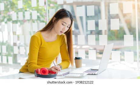 Beautiful Asian woman wearing a yellow shirt and headphones using a laptop in a cafe, write a note Charming female student in language learning, watch online webinar, audio listening course, education