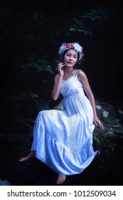 Beautiful Asian woman with white traditional dress sitting on rock in forest at night