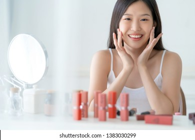 beautiful asian woman white tshirt smile with happiness hand hold blush on and makeup cosmetic items in bedroom with healthy  face skincare concept