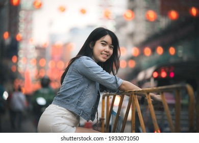 Beautiful Asian woman who has long hair travels to the festival at Yaowarat Chinatown in Thailand. Street photography of traveler woman at night.