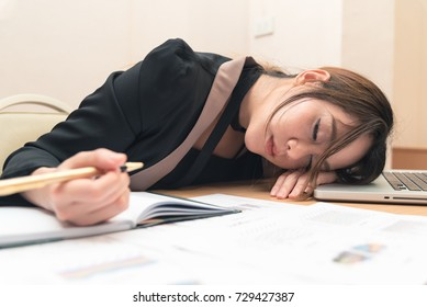 Beautiful asian woman woker sleep on notebook with pen in hand at office, cause tired overworked
