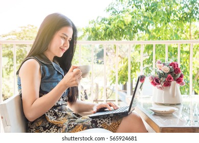 beautiful asian woman working outdoor with laptop relaxing in a coffee
