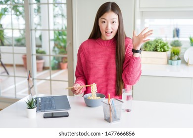 Beautiful Asian woman working using laptop and eating asian noodles very happy and excited, winner expression celebrating victory screaming with big smile and raised hands