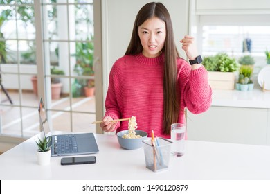 Beautiful Asian woman working using laptop and eating asian noodles annoyed and frustrated shouting with anger, crazy and yelling with raised hand, anger concept