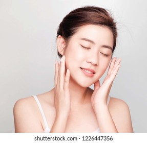 Beautiful asian woman ,young asian girl with clean and bright skin, Cosmetic Beauty Concept,hands touch on the cheek,closed eyes and friendly face isolated on grey background