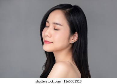 Beautiful Asian woman with youthful radiant face skin for cosmetic and beauty concepts isolated studio shot