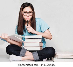 Beautiful asian woman,long hair wore black glasses and blue t-shirt,Student Read the exam preparation book,Serious expression