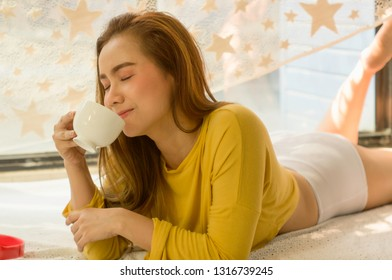 Beautiful Asian women with a cup of white coffee and headphones,With relax after waking up on bed in the bedroom of the house,concept of relaxation and charging for life during the holiday.