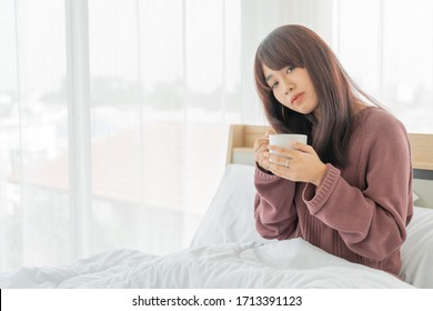 beautiful Asian women drinking coffee on bed in the morning