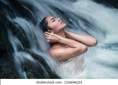 Beautiful asian women girl with tan skin and wearing a white swimsuit. She's closing her eyes, use hands stroking on black hair by lonely, waterfall was blowing strongly relax people travel nature.