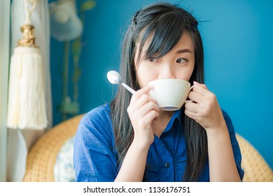 Beautiful asian women hold cup of hot coffee in vintage cafe