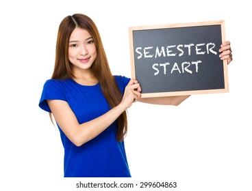 Beautiful asian women asian hold wood blackboard showing phrase of semester start