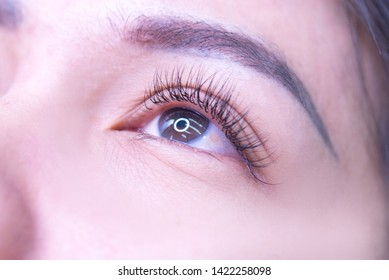 Beautiful Asian women with long eyelashes in the beauty salon, eyelash extension procedures, close-up eyelashes