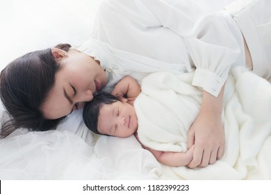 Beautiful asian women mother with long black hair in the white pajamas. mom looking at newborn infant with love, while a baby sleeping in her arm with warm, safe, comforted resting on the clean bed.