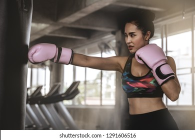 Beautiful Asian women are punching sandbags in the gym, exercise ideas, weight loss, muscle building and self defense.