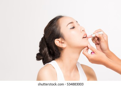 Beautiful Asian women with pure face and Make up artist apply lipstick on her labia with a copy space