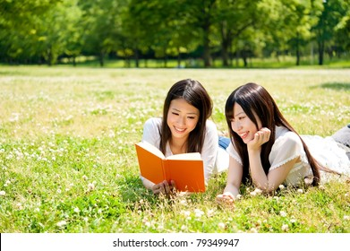 beautiful asian women reading a book in the park