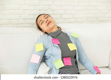 Beautiful asian women return from work She is very tired And sleeping on the sofa On the body is filled with  Post-it Notes