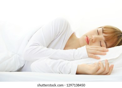 Beautiful asian women with short hair, wearing white shirts Sleeping in a white bed in the morning, Relax and sleep well