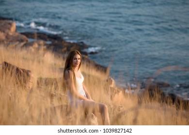 Beautiful Asian women sitting on rock beach. rerax time concept