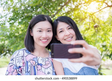 Beautiful Asian women taking their photo by smart phone in park