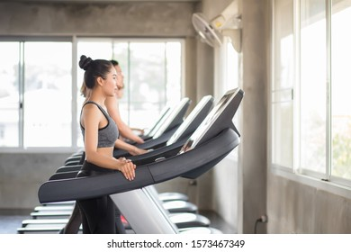 Beautiful Asian women Thai people have tan skin, long hair and tied hair in a sports bra doing exercise by running on the electric treadmill in the fitness room in Thailand.