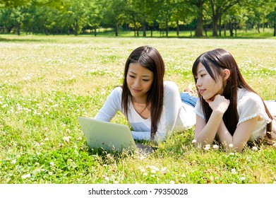 beautiful asian women using laptop in the park