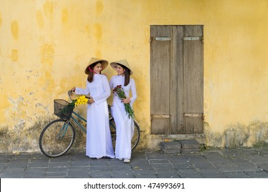 Beautiful asian women with Vietnam culture traditional dress, Ao dai is famous traditional costume, vintage style, Hoi an Vietnam town.