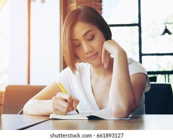 A beautiful Asian women wear white shirt and write a diary in a book in her holiday and look happiness.