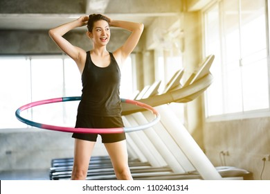 Beautiful Asian women wearing sportswear. Playing hula hoop in the morning gym. Helps to burn excess fat in the body. Strengthens the muscles of the body. Increases blood flow to the brain.