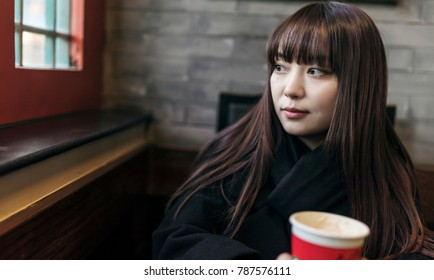 Beautiful Asian women who drink coffee in the cafe