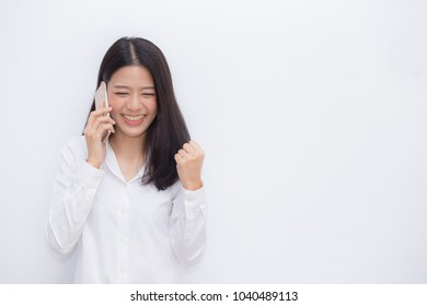 Beautiful asian young businesswoman excited and glad of success taking mobile phone on cement background, career freelance business concept.