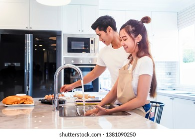 Beautiful asian young couple helping to cooking bekery in the kitchen at home. Man happy to helping.