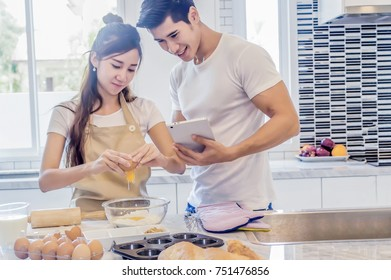 Beautiful asian young couple helping to cooking bekery in the kitchen at home.Man is looking tablet.