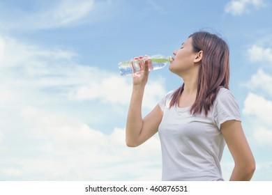 Beautiful asian young girl drinking water outdoor