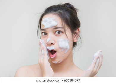 beautiful Asian young girl enjoy skin care product that she apply on her facial skin