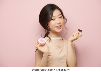 Beautiful Asian young Korean woman applying blush on her cheeks