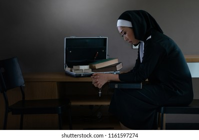 Beautiful asian young nun in religion black suit in robes holding a cross and praying on the dark background of the wall