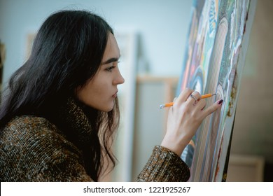 beautiful asian young woman artist paints a picture in the workshop