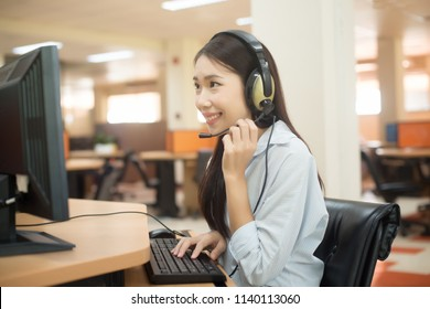 Beautiful asian young woman Customer service executive working at office by the table in headphones. Call center