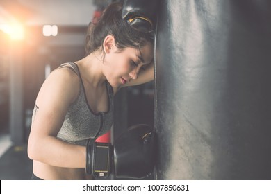 Beautiful asian young woman doing exercise with Thai boxing (Muay Thai) equipment in gym. Health and fitness concept. Vintage color and warm lens flare filter effect