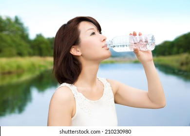 Beautiful asian young woman drinking a bottle of water in the nature.